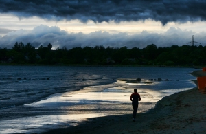 Runner's silhouette on the stormy beach, stormy clouds on the sky, light reflecting on the sea